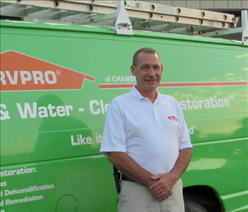 A male with brown hair, white shirt standing in front of the Green SERVPRO van.