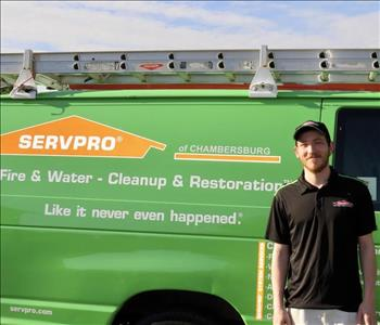 A young male in front of the SERVPRO green truck in his uniform.